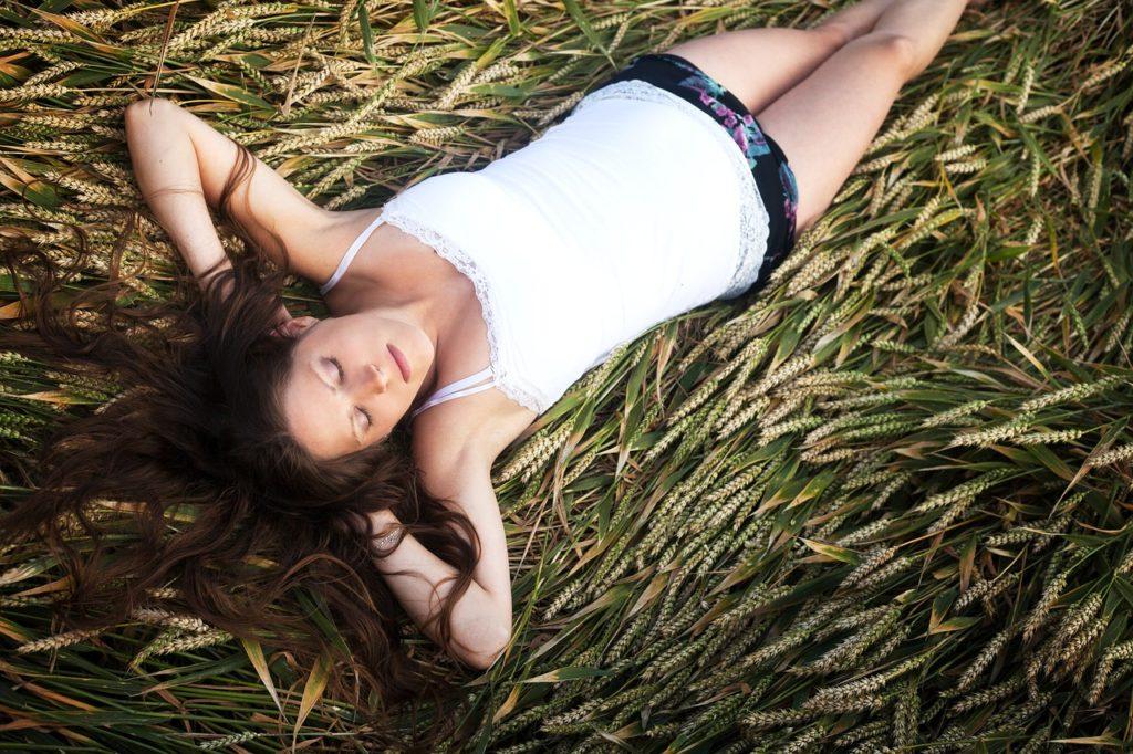 Schwangere Frau liegt im Gras - Schwangerschaftswoche 1 bis 12