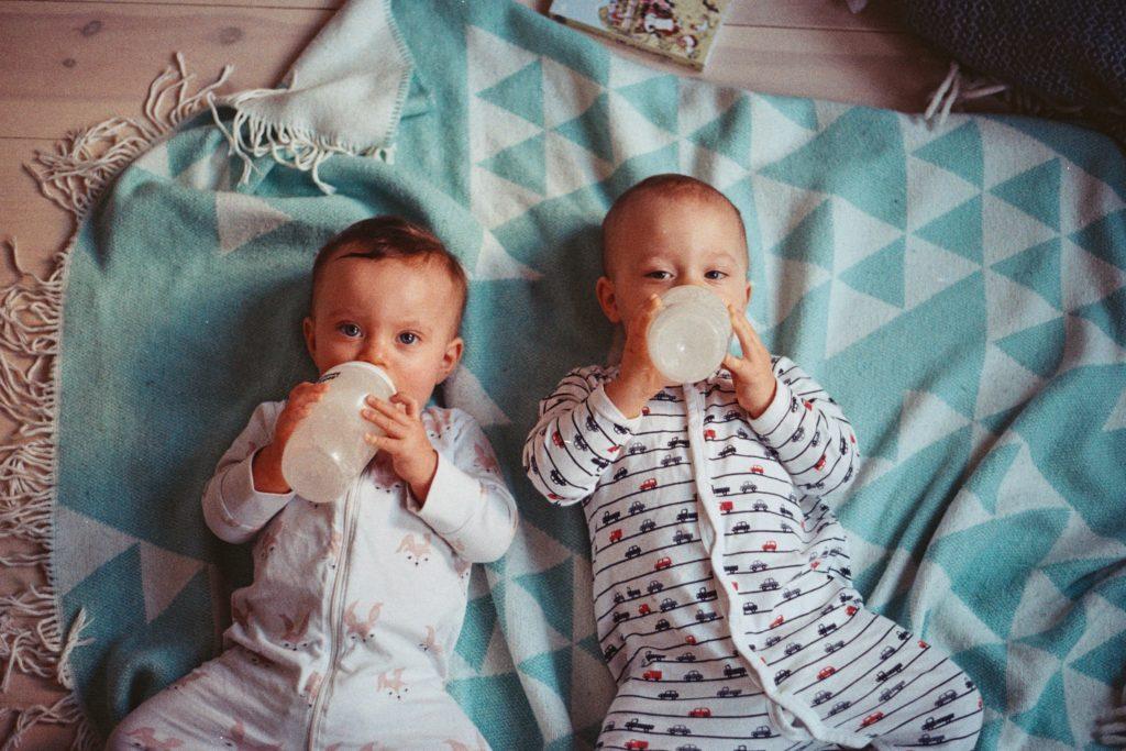 Zwei Babys trinken aus der Flasche