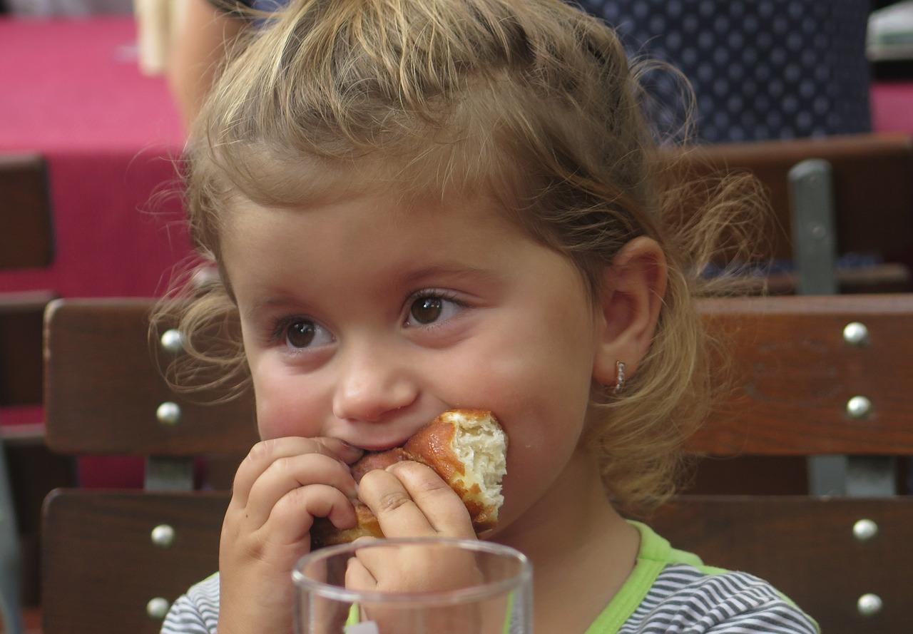 Kind isst ein Croissant - Babynahrung